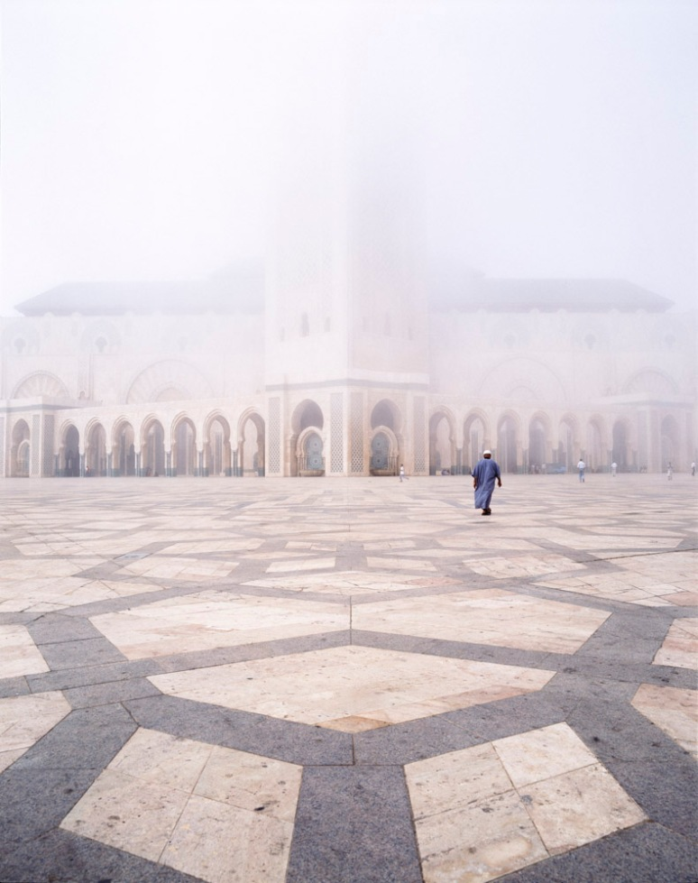 The Hassan II Mosque partially concealed by fog with a man wearing a Jalaba.
