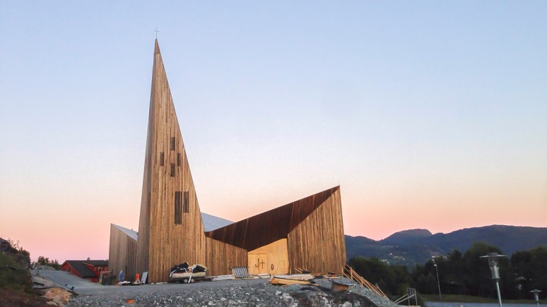 Overview of the church during construction at dusk.