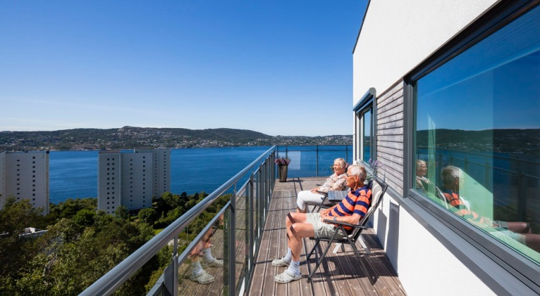 Retired couple enjoying the magnificent view from their new flat in Bergen.