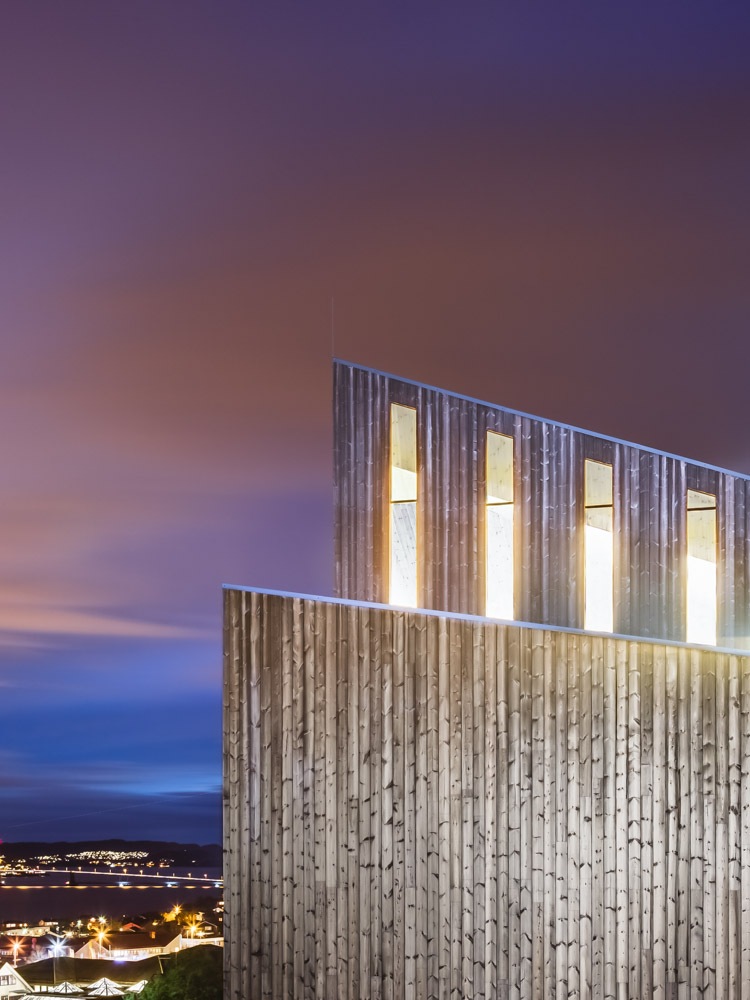 Window and cladding detail at night of Knarvik Church / Knarvik Kirke, Norway designed by Reiulf Ramstad Arkitekter.