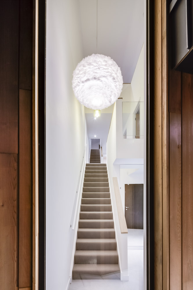 Looking up the stairs at The Woods residential property designed by Scott Brownrigg, Bedfordshire, UK.