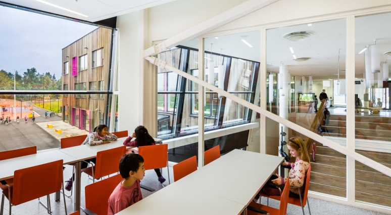 Cafe with multiuse hall in the background at Veitvet Skole designed by Link Arkitektur, Oslo, Norway.